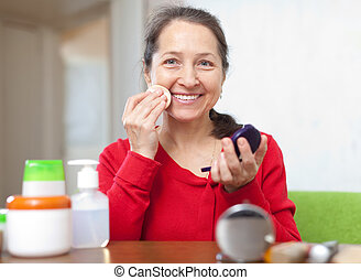 Happy mature woman puts facepowder - Happy mature woman in...