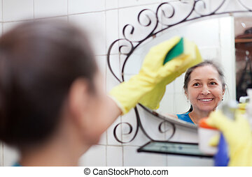 woman cleans mirror with sponge in bathroom at home Focus on...