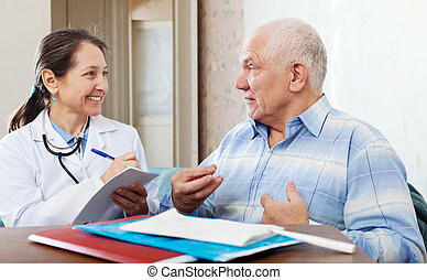 friendly mature doctor talks with senior man - friendly...