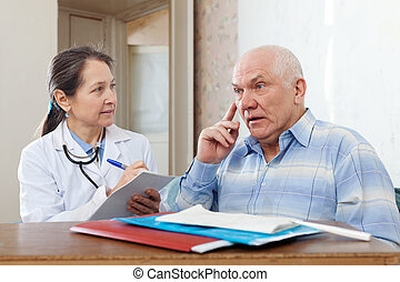 Woman doctor and senior patient near table with documents