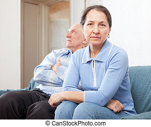 Family quarrel - Mature couple after quarrel in living room...