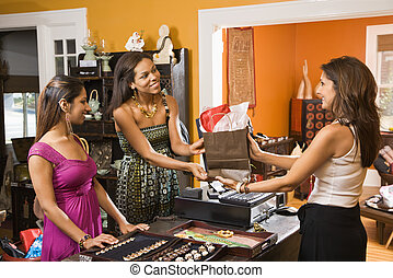 Customers making purchase. - Two women making purchase from...