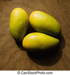 Home decor. - Still life of three wooden mangoes on plate.