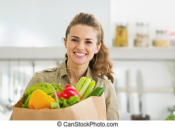 Happy young housewife with shopping bag full of vegetables