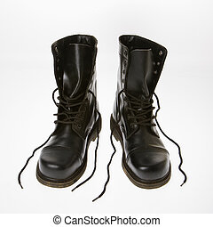 Combat boots. - Black leather boots with laces untied.
