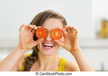 Happy young woman holding two slices of tomato in front of...