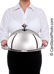 Waitess serving a silver dome or cloche