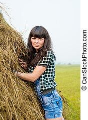Portrait of pretty brunette standing near the haystack -...
