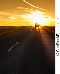 Truck traveling at sunset.