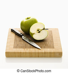 Cut apple - Still life of green apples and knife on cutting...