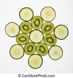 Fruit pattern - Kiwi and lime fruit slices arranged on white...