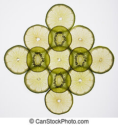 Fruit slices. - Lime and kiwi fruit slices arranged on white...