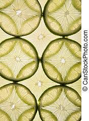 Citrus slices. - Lime slices arranged in design on white...