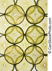 Fruit slices - Lime slices arranged in design on white...