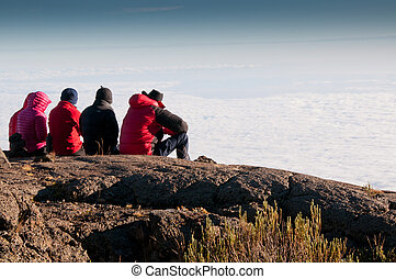 Team gazing over clouds - A team of trekkers gazing over the...