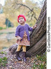Cute little girl in a red cap near lake at the autumn park