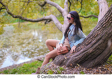 Young cute girl enjoying holiday in autumn park near the lake