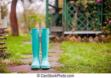 Bright mint rubber boots in the garden summer house...