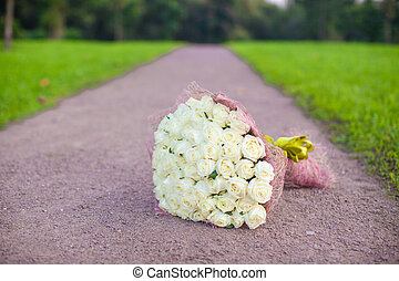 Incredibly beautiful large bouquet of white roses on a sandy...