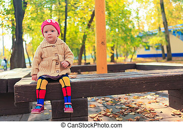 Little beautiful girl sits on a bench in autumn park
