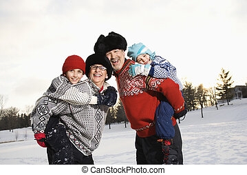 Family piggybacking - Caucasian middle aged parents carrying...