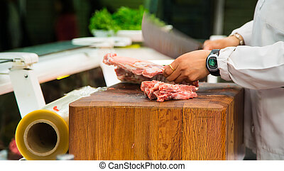 Butcher Cutting Meat with Cleaver - Butcher chopping meat on...