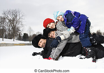 Family stacked in snow.