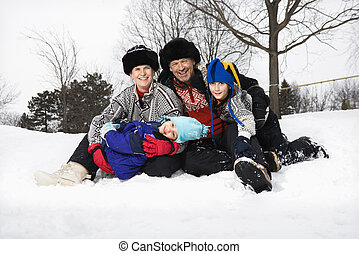 Family sitting in snow.