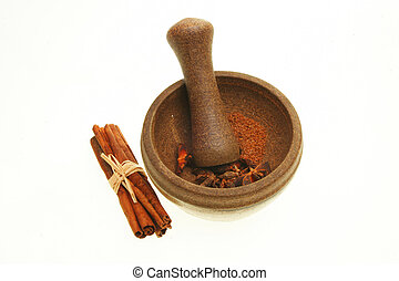 Pestle and mortar with spices isolated on white