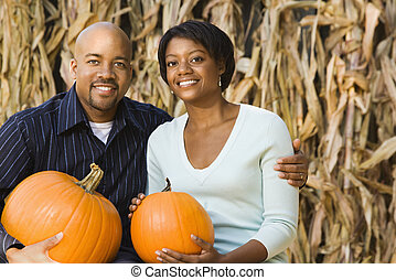 Fall couple portrait. - Happy smiling couple sitting on hay...