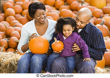 Family at Halloween. - Happy smiling family sitting on hay...