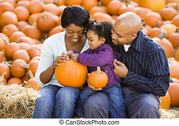 Family holding pumpkins. - Happy smiling family sitting on...