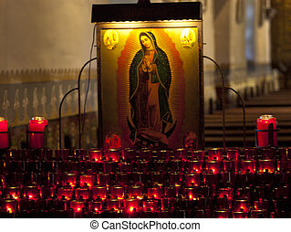 Mary and the candles - the virgin Mary picture in front of...