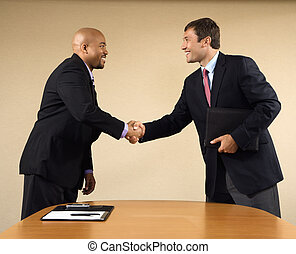 Business meeting - Two businessmen in suits shaking hands...