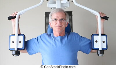 Senior Chest Exercises - Elderly man uses chest exercising...