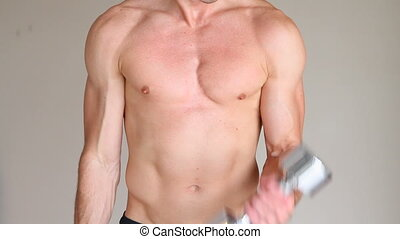 Man Dumbbell Exercising - Muscular young adult exercises...
