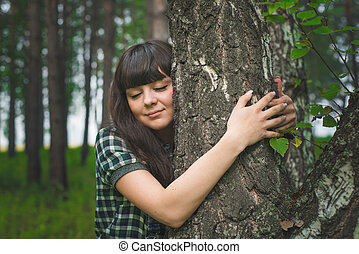 Portrait of beautiful girl hugging birch in the forest -...