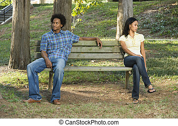 Couple sitting apart. - Man and woman sitting on opposite...