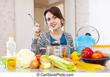 woman cooking soup - woman cooking veggie soup with laddle...