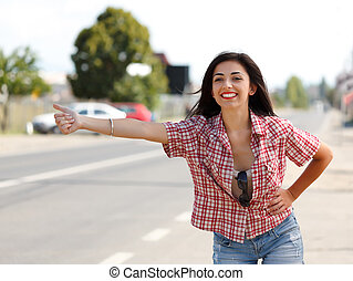 Hitch hiking - Smiley attractive woman hitch-hiking on the...
