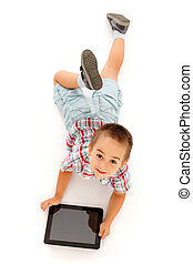Kid using tablet PC - Beautiful kid laying and enjoying...