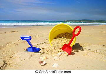 Child's beach bucket and spade on a sandy beach with...