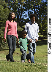 Family in park. - Parents and young son walking in park...