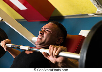 Effort On The Bench Press - Bodybuilder In Gym Exercising On...