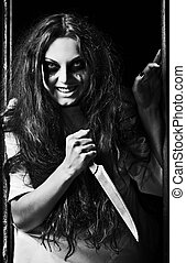 Horror style shot: crazy evil girl with knife in hands....