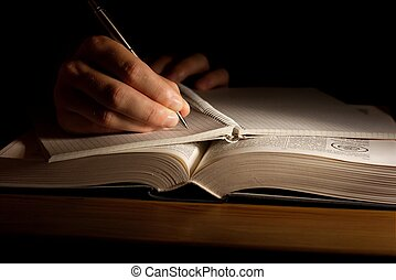 Book - Hand with pen taking notes from an open book