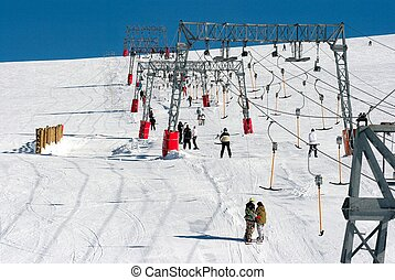 Skiing - Skiers using a ski lift at a winter resort