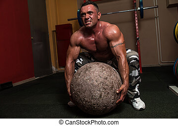 Bodybuilder Trying A Strongman Exercise - Muscular Man...