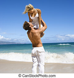 Man holding woman. - Man holding woman up in air as they...