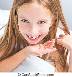 girl showing her teeth - little girl showing her teeth that...